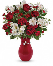 Perfectly romantic! Steal her heart this Valentine's Day with this majestic mix of classic red roses and delicate white alstroemeria, hand-delivered with love in our exclusive hand-glazed vase. Wrapped in a shimmering metallic band adorned with a pair of hearts, it's an extra-special reminder of your love. This heartfelt bouquet includes red roses, white alstroemeria, red miniature carnations, lemon leaf and pitta negra. Delivered in the Pair Of Hearts vase. Orientation: One-Sided