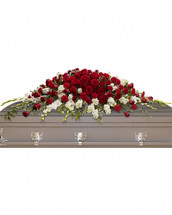A traditional tribute that communicates deep love and eternal commitment. This dramatic red and white casket spray is ideal for a full couch or closed casket, mixing dozens of deep red roses with the pure white beauty of gladioli and stock. Red roses and carnations are paired with snow white gladioli and stock, then accented with greens including variegated ivy and salal.