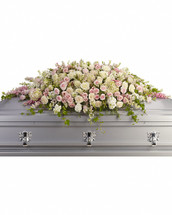 A graceful and magnificent cascade of delicate pale pink, white, and crème flowers conveys everlasting affection for the radiant spirit being honored, and gently eases sorrow for those paying respect. Soft and feminine, this casket top display is composed of flowers such as pink hydrangea, roses and larkspur, along with white roses, stock and waxflower, accented by ivy, parvifolia eucalyptus and leatherleaf fern. Orientation: N/A