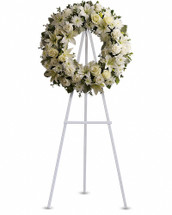 Fragrant and ethereal white blossoms set among a ring of soothing greens form a classic wreath certain to evoke the pure heart and gentle spirit of a loved one - and offer consolation during a funeral or wake. Delivered on an easel, a standing wreath comprising fresh flowers such as white roses, asiatic lilies, carnations and chrysanthemums, as well as greens including salal, oregonia and dusty miller. Orientation: One-Sided