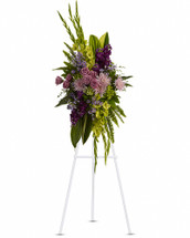 Soft lavender flowers - roses, fuji chrysanthemums and asters - blend with rich purple stock, yellow gladioli and majestic green hydrangea in this bold floral celebration of life. This stunning standing spray incorporates lush tropical greenery. Includes lavender larkspurs, roses, carnations and asters, plus, green cymbidium orchids and fuji chrysanthemums. Orientation: One-Sided