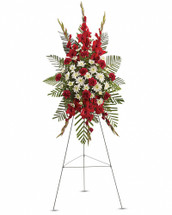 A beautiful complement to the memorial service, this gorgeous spray of red and white floral favorites will be deeply appreciated by the family during their time of loss. The magnificent spray includes red gladioli, red carnations and white cushion spray chrysanthemums, accented with emerald palm and leatherleaf fern. Orientation: One-Sided