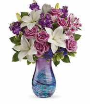 "Lavender roses, white asiatic lilies, purple alstroemeria, purple stock and purple seafoam statice are arranged with variegated pittosporum and lemon leaf. Delivered in an Artful Elegance vase. Approximately 15 1/2"" W x 20 1/2"" H"