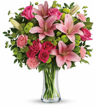"""This fabulously feminine bouquet features hot pink roses, hot pink spray roses, pink asiatic lilies, pink carnations, green button spray chrysanthemums, bupleurum, huckleberry and lemon leaf. Delivered in a clear glass vase. Approximately 17 1/2"""" W x 20"""" H"""