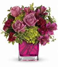 "Green miniature hydrangea, lavender roses, purple alstroemeria and maroon miniature carnations accented with greens. Delivered in Teleflora's glass fuchsia cube. Approximately 10 1/2"" W x 11 1/2"" H"