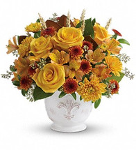 Invigorating as an autumn sunrise, this golden fall bouquet will lighten up any room with its radiant roses arranged in an antiqued French Country pot.