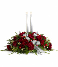 The stunning bouquet includes dark red spray roses, maroon carnations, ming fern, green rhamnus, cedar and large red berries. Comes with two 12 silver taper candles. Approximately 22 1/2 W x 16 1/2 H