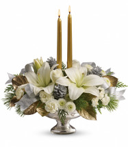 "This stunning arrangement includes white roses, white asiatic lilies, white miniature carnations, white button chrysanthemums, flat cedar, white pine and lemon leaf, accented with small silver pinecones, gold taper candles and silver ribbon. Delivered in an exclusive Mercury Glass bowl. Approximately 16"" W x 16"" H"