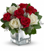 "The delightful holiday bouquet features red roses and white roses accented with assorted greenery. Approximately 11"" W x 10 3/4"" H"