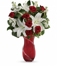 Romantic red roses and pure white lilies are the ultimate show of love and tenderness this Valentine's Day. Artfully arranged in a showstopping art glass vase with hand-applied glass ribbon, this luxurious gift will warm her heart for years to come.