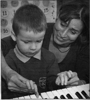 Elza Lusher gives Haden Stevens, four, his first piano lesson