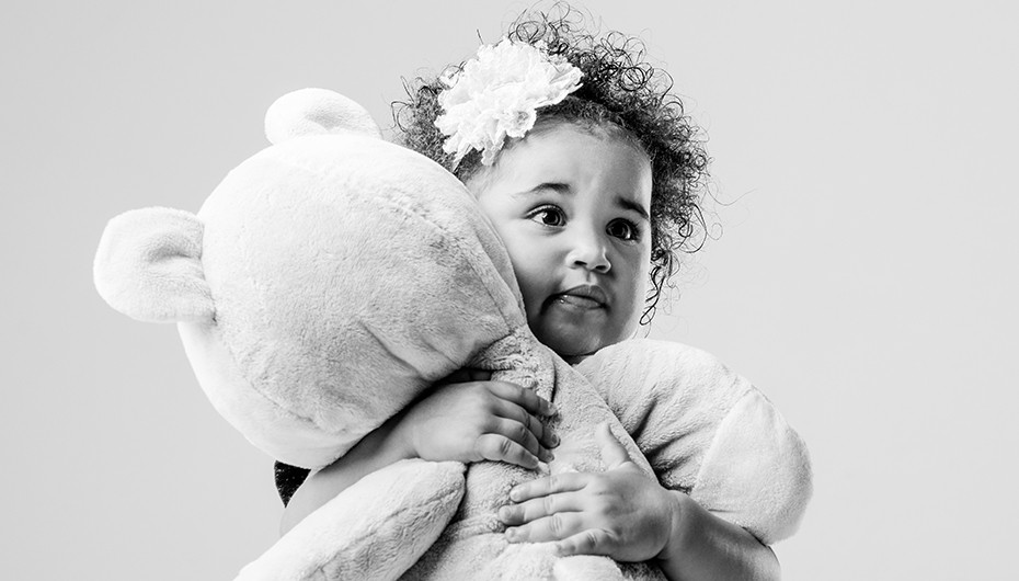 Adorable little girl cuddling teddy bear picture in black and white by Emotion Studios.