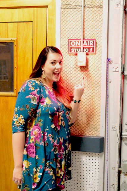 """Cordial Lee Owner, Shelby Packer, pointing to the """"On Air"""" Light just outside the studio door. You can hear a pin drop when this light it on."""