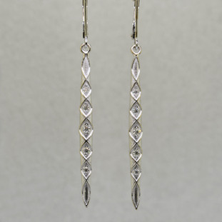 You will feel like a Princess wearing these striking, long dangling diamond earrings. Set with .20ct. T.W. of Ideal cut Diamonds, in 14 karat Brilliant White Gold, dangling from lever backs. Earrings measure 2 1/4 inches long.  Designed, and created in our studio by the artist Stuart J.