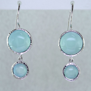 Light, and breezy these rhodium plated Sterling Silver earrings elicit a beachy feel. Set with soft cabachon milky blue Calcedony gemstones, dangling on Sterling Silver wires. Earrings measure 1 inch long.  Handcrafted in Northern Spain.