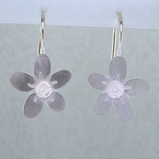 Sweet and simple daisy earrings in Sterling Silver, hanging on wires. Perfect for a first pair of earrings. Measure 1 inch long.  Handmade in Istanbul, Turkey.