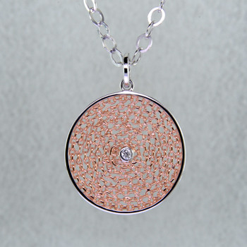 You will love this Sterling Silver circular pendant. Light and airy, this fun pendant is crafted in rhodium and rose gold plated Sterling Silver, with a fine filigree center, and a .04ct. round brilliant cut diamond. Pendant measures 1 inch in diameter, and includes a Sterling Silver round open link chain, 18 inches long. Handcrafted by artists in Northern Spain.