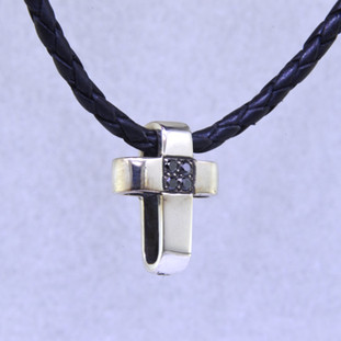 For the modern, spiritual man with a little edge, this solid Sterling Silver cross is accented with 4 black diamonds in the center. Comes with a black leather cord. Pendant measures 3/4 inch long.  by David Heston of San Rafael, California.