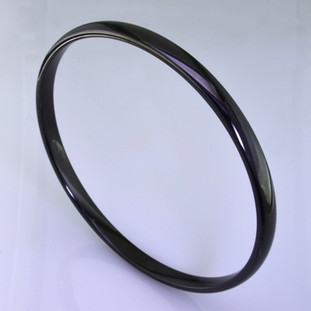 This new age bangle bracelet is made from space age Gem Ceramique ceramic, and is perfect for stacking, or distinctive on it's own. Silky smooth, and bright glossy black, it measures 1/8 inch wide.  Also comes in many other colors. Just ask us for your favorite.   Made in Camden, Maine by award winning designer Etienne Perret.