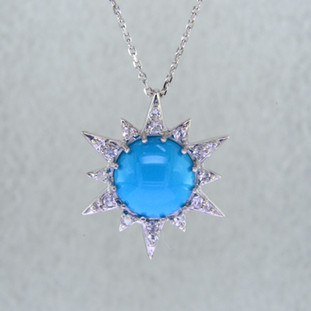 Effortlessly chic, this beautiful Turquoise star pendant in Sterling Silver goes anywhere you do. Set with a 10mm round sultry blue Turquoise, surrounded by brilliant white Sapphires. Hangs on a Sterling Silver .07mm anchor chain, 18 inches long. Pendant measures 3/4 inch long.  Handcrafted by artists in Montreal, Canada.