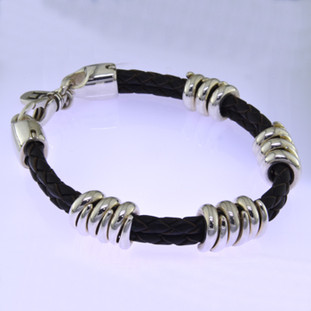 Edgy and modern, this braided leather and sterling silver man's bracelet makes a statement in a classy, understated way. The genuine leather measures 6.5mm in diameter, with solid sterling silver coils, and a sturdy clasp. Will fit an 8 inch wrist, and can be sized down only.  by David Heston of San Rafael, California.