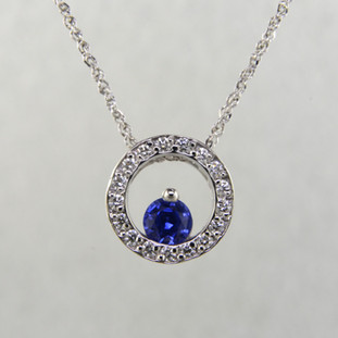 This beautiful one-of-a-kind circle pendant is a classic, timeless design. Crafted in 14 karat white gold, with .17ct. T.W. Ideal cut diamonds encircling an exquisite cornflower blue Sapphire gemstone measuring 4mm. Includes a 14 karat white gold sparkle wheat chain, 16 inches long.  Designed, and created in our studio by the artist Stuart J.