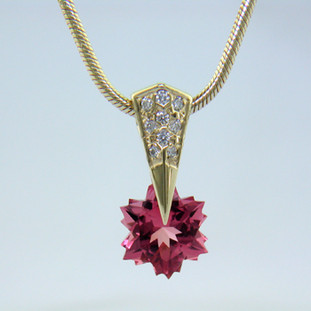 "Our fabulous, exclusive, patented, one-of-a-kind Piercette® pendant, set with .09ct. of Ideal cut, pave set diamonds, and a custom cut snowflake Pink Tourmaline. Measuring 8mm, this vibrant pink tourmaline has been expertly cut, just for us, in Canada, by third generation gem cutters. Includes a 14 karat yellow gold, 1.3mm diameter smooth snake chain, 16 inches long. Pendant measures 5/8"" long. Designed and handmade by the artist Stuart J.  A Piercette® is a patented method of setting, with a gemstone that moves. The gem is set so that it swivels with every movement of the wearer, exhibiting extra sparkle."