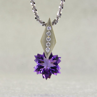 "This Amethyst snowflake and Diamond Piercette® pendant will melt your heart. Set in 14 karat white gold, with an 8mm custom cut deep purple Amethyst snowflake, dangling from a kite shaped bail, sprinkled with .05ct. T.W. Ideal cut Diamonds. The Amethyst snowflake gemstone is custom cut, exclusively for us, in Canada. Includes a 14 karat white gold 1.3mm diamond cut wheat chain, 18 inches long. Pendant measures 5/8"" long. Designed and handmade by the artist Stuart J.  A Piercette® is a patented method of setting, with a gemstone that moves. The gem is set so that it swivels with every movement of the wearer, exhibiting extra sparkle."
