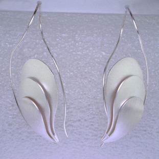 These sculptural Sterling Silver earrings are amazing. Handmade in Istanbul, beautiful triple tier design, with a soft feel and bold look. These earrings look like true art. The wire feeds through the ear, hanging in the perfect place. Definitely a statement piece. These earrings measure 2 1/2 inches long.