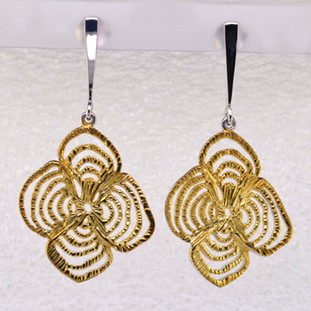 These delicate looking, yet sturdy earrings showcase a striking flower motif. Great style for any occasion. Gold plated Sterling Silver, these earrings measures 1 3/4 inches long, and hang on posts.  Handcrafted in northern Spain.