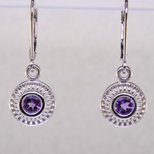 "Blending traditional and modern, these earrings dazzle for day or night. Hand crafted in 14 karat white gold with sparkling 4mm Amethyst buff top gemstones dangling on lever backs. Earrings measure 1"" long.    Designed, and created in our studio by the artist Stuart J."