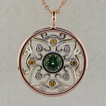 This stunning tourmaline, sapphire, and diamond pendant will take your breath away. A one of a kind piece created in 14 karat rose, and white gold, with an open floral design inspired by vintage artwork. Set with a stunning 1.12 carat green tourmaline in the center, and accented with .12ct. of ideal cut diamonds, and 4-yellow sapphire gemstones. This pendant hangs on a a very unique 18 inch, 14 karat rose gold open link chain, and measures 1 1/4 inches in diameter.  Designed, and created in our studio by the artist Stuart J.