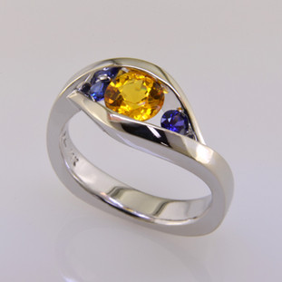 This elegant two color sapphire ring has a low profile, is easy to wear, and super comfy. Priced here in 14 karat white gold with a 1.09 carat sunny yellow round sapphire, and 2 amazing round deep blue sapphires. (We can make it in any metal, and for any size diamond or colored gemstone). This is truly a timeless design, with no prongs to catch. A matching shadow wedding band is also available, if you like this as an engagement ring  This custom designed gemstone ring is individually crafted to be Perfectly You, and is a one of a kind piece. Call us for more information about how we can customize this design Just For You. Designed, and created in our studio by the artist Stuart J.