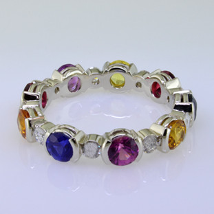 Want to brighten your day?  This amazing band will do it.  Feel special with this one of a kind eternity band with multi color sapphire gemstones.  All the colors of the rainbow,  This eternity band has .46ct. of sparkling diamonds and is surrounded by 9-round colorful sapphires.  This ring is a size 7, but if you love it we can make it in your finger size.  Just ask us, and we only need about 3-4 weeks to complete. Call us for pricing.  Designed and created by master jeweler Stuart J.