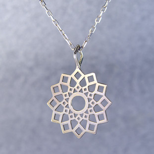 Playful and bright, this snowburst pendant is a delight to wear. Sterling Silver with a snowflake pattern and hangs on a 1mm Sterling Silver oval link chain, 18 inches long. Pendant measures 1 1/2 inches long.  Created and handmade by master jeweler Stuart J.
