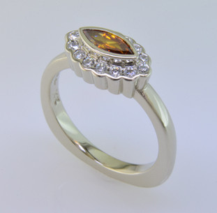 Born into our family on April 25th (with a Diamond Birthstone), and weighing in at a modest .52 carat total weight, this spectacular modern diamond halo engagement ring is set with a .29 carat natural color orangy yellow marquise diamond. We cradled it with .23 carat of colorless ideal cut diamonds, set in white gold with no prongs to worry about. Truly, our new baby will be loved by all. This one fits a size 6 finger, but we will happily make Ginger to fit your finger.  We made a matching set of twin wedding rings in 18 Karat yellow gold (shown), that compliments this engagement ring perfectly. They are priced seperately here Ginger Wedding Ring.  As with all of our designs, we will make this any way you like, with any gemstones you like, including yours.  Custom designed and hand crafted in our studio by the artist Stuart J.
