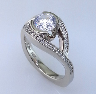 We took this diamond engagement ring design from our family archive, and jazzed it up to this new sparkly, modern, and very beautiful version. Still classic and timeless, with no prongs to catch, this ring is lined with .26 carat total weight of ideal cut diamonds, set in 14 karat white gold. The center diamond weighs in at 1.00 carat (priced separetly). This beautiful diamond ring will never go out of style, and is a dream to wear. A matching diamond wedding ring is also available. We can also make this ring for any size center, including yours. Oh, and we will customize it any way you wish!  Made in our studio by the artist Stuart J.