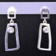 Fun, and funky earrings for the adventurous girl. Sterling silver dangles with rectangular shapes, bezel set with 2 colorless topaz gemstones resting on posts. Measures 1 inch long, and created in studio by french jeweler Sean Hill.