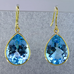 Elegant, sophisticated, 18 karat yellow gold drop earrings with thin bezels holding them in just enough to let the stones shine. 39.30ct. of pear shaped blue topaz gemstones, hanging on wires. Measure 1 1/2 inches long.  Handmade in Brazil.