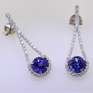 Sparkly, elegant, and sensual only begin to describe these Diamond and tanzanite gemstone earrings. Handcrafted in 14 karat White Gold with  .88cts. of fine Ideal cut Diamonds and 2 perfectly matched, super fine, rich blue tanzanites totaling 3.04ct.. Need we say more? Earrings measure 1 1/4 inches long, and hang on posts.   Designed and handmade by the artist Stuart J.