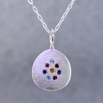 "This sweet pendant shimmers when you wear it. Beautiful sterling silver medallion sprinkled with aquamarine,ruby,blue sapphire,amethyst,pink tourmaline, and blue zircon gemstones set in a starburst pattern, with a glowing citrine in the center, hanging on a 1.4mm oval sterling silver cable chain. 18"" long.    Wear it as a birthstone pendant too, and customize it just for you.  Call for prices on your special birthstones. Special orders will take 2-3 weeks  Designed and created in our studio by the artist Stuart J."