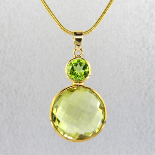 "Elegant, sophisticated, 18 karat yellow gold drop pendant with thin bezels holding them in just enough to let the stones shine. 17.35ct. of round shaped peridot and lemon citrine gemstones, hanging on a 18 karat smooth snake chain in 18"". Measure 1 1/2 inches long.  Handmade in Brazil."
