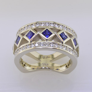 With this spectacular diamond and blue sapphire anniversary ring on your finger, you will feel like royalty, and be the envy of all of your friends. With .52 carats of Ideal cut diamonds, round diamonds cascading down the outside edges, and beautiful blue sapphire princess cuts down the center, Sparkle is this rings middle name. There are no prongs to catch, and it is very comfortable to wear. Made with a mix of round diamonds and princess cut diamonds, it is a feeling of traditional with a modern flare. This custom designed diamond anniversary ring is individually crafted to be Perfectly You. Call us for more information about how we can customize this design Just For You.   Designed, and created in our studio by the artist Stuart J.  This diamond anniversary ring is priced in 14k gold, and can be made in any karat or color, and in platinum. Makes a great anniversary gift for 10, 20, 30 or more years together.