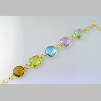 Extraodinary, 18 Karat Yellow gold bezel set multi color bracelet, with 106.60ct. of Cognac Quartz,Lemon Citrine, Blue Topaz, Green Amethyst, and Lavender Amethyst gemstones.  This bracelet is simply spectacular. Handmade in Brazil. 7 1/2 inches long.