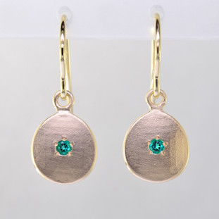 These sweet gemstone earrings shimmer when you wear them. Beautiful in rich 14 Karat yellow gold, these medallions with chatham created emerald gemstones in the center( 2mm), hanging from 14 Karat yellow gold wires.  Earrings measure 3/4 inch long. Available in other colors. Please call for pricing. Designed and created in our studio by the artist Stuart J.  Chatham Gemstones are also available in Ruby, Sapphire, and Alexandrite.                                                                                                                                                                                                                                                                                                                                                                                    Chatham® Created Gemstones are grown in carefully controlled laboratory conditions. They are chemically and optically identical to their natural counterparts, yet cost much less. Because the environment in which they are grown is controlled, the imperfections often found in natural gemstones, are absent in Chatham® Created Gemstones. Because of this, and superior cutting, Chatham® gems exhibit the color and sparkle of the finest natural gems. Each one comes with a Certificate of Authenticity, and a Lifetime Warranty.
