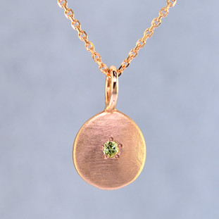 This sweet gemstone pendant shimmers as you wear it. Beautiful in 14 Karat Rose gold, this medallion has a beautiful peridot gemstone in the center, and hangs on a 1 mm 14 karat rose gold wheat chain,24 inches long.Pendant measures 3/4 inch long. Available in other colors. Please call for pricing.  Designed & Created in our studio by the artist Stuart J.
