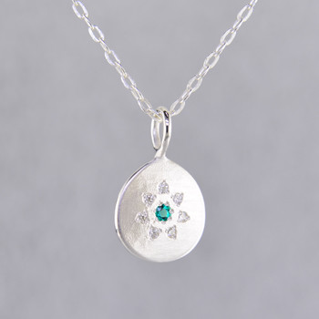This sweet pendant has a special, hand applied finish that shimmers when you wear it. Beautiful and shiny sterling silver drop, sprinkled with .06 carat total weight of ideal cut diamonds, with a glowing Chatham® created emerald gemstone in the center. Comes with an 18 inch, sterling silver oval cable chain. Pendant measures 5/8 inch long.  Chatham Gemstones are also available in Ruby, Sapphire, and Alexandrite.  Designed and created in our studio by the artist Stuart J.  Chatham® Created Gemstones are grown in carefully controlled laboratory conditions. They are chemically and optically identical to their natural counterparts, yet cost much less. Because the environment in which they are grown is controlled, the imperfections often found in natural gemstones, are absent in Chatham® Created Gemstones. Because of this, and superior cutting, Chatham® gems exhibit the color and sparkle of the finest natural gems. Each one comes with a Certificate of Authenticity, and a Lifetime Warranty.