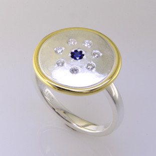 This sweet ring has a special, hand applied finish that shimmers when you wear it. Beautiful, rich sterling silver framed in rich 18 karat yellow gold, sprinkled with 7 ideal cut diamonds weighing a tenth of a carat, with a Chatham created deep blue sapphire gemstone in the center. This one is a size 7, but we can make it in any size. Ring top measures 5/8 inch in diameter.    Chatham Gemstones are also available in Ruby, Sapphire, and Alexandrite.  Designed and created in our studio by the artist Stuart J.  Chatham® Created Gemstones are grown in carefully controlled laboratory conditions. They are chemically and optically identical to their natural counterparts, yet cost much less. Because the environment in which they are grown is controlled, the imperfections often found in natural gemstones, are absent in Chatham® Created Gemstones. Because of this, and superior cutting, Chatham® gems exhibit the color and sparkle of the finest natural gems. Each one comes with a Certificate of Authenticity, and a Lifetime Warranty.