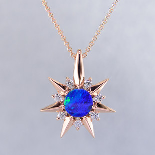 This beautiful pendant twinkles just like the stars at night. Our Starflake(tm) andamooka opal and Diamond pendant is made in 14 karat rose Gold, set with a mesmerizing 8mm blue round opal , surrounded by .28ct. T.W. Ideal cut Diamonds. Includes a 14 karat rose Gold foxtail chain, 18 inches long. Pendant measures 1 inch long.  Designed, and created in our studio by the artist Stuart J.