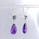 "We picked these beautiful Amethyst drops from Zambia because the color was so rich!  We added these beautiful light Blue Topaz for a perfect match.  Created in 14 Karat white gold, with these beautiful blue topaz buff tops set in bezels, and the amazing deep purple amethysts drops making these earrings the perfect accessory to any outfit!  These drop dangle earrings measure 1 1/4"" long, and hang on 14 Karat white gold wires.  Designed, and created in our studio by the artist Stuart J."